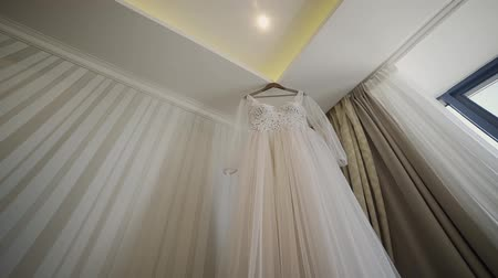 koronka : Beautiful wedding dress hanging in a large chandelier.