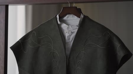 casual wear businessman : A mans jacket hangs on a hanger in the room.