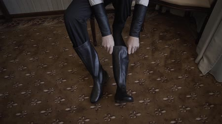 cipőfűző : man puts on his black leather boots.