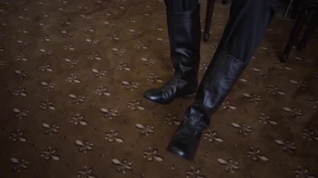 sıkmak : man puts on his black leather boots.