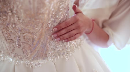 irreconhecível : Very beautiful girl touches her wedding dress.