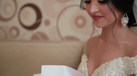 невеста : Very beautiful bride opens and reads a letter from a loved one. Стоковые видеозаписи