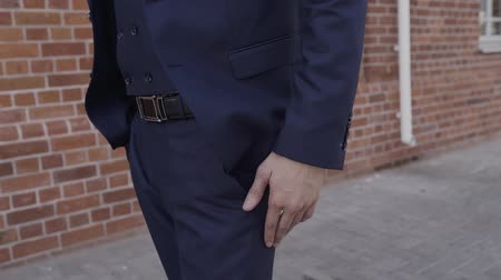опытный : Man in black suit put his hand in to the pocket of trouses. Closeup.
