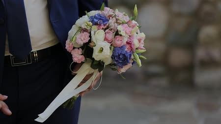 コミットメント : On a wedding day wedding bouquet in hands of the groom. 動画素材