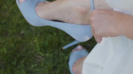 дорогой : Woman puts on shoes hands close up shallow depth of field. Bride fastens zipper on luxurious high heeled sandals sitting in gorgeous white gown getting ready prepared for dancing at wedding ceremony.