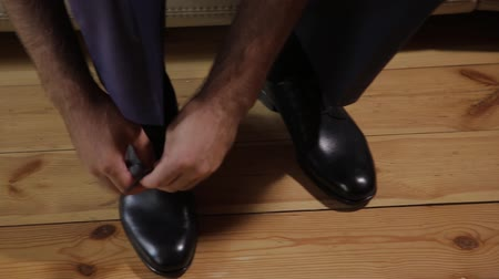 tying : Young man tying shoelace on sport shoes indoors, closeup. Stock Footage