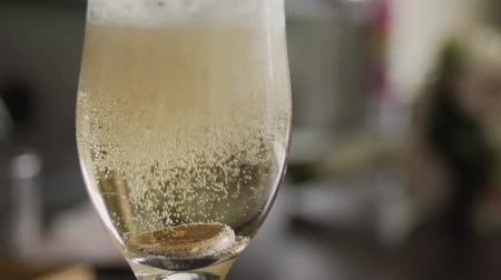 champagne flute : Gold wedding rings fall into a glass of champagne.