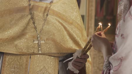 christening : The Sacrament of Baptism in the Orthodox Church. Close-up of a priest lighting candles in a font.