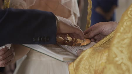 обряд : the priest conducts the wedding ceremony, serves wedding rings. Стоковые видеозаписи