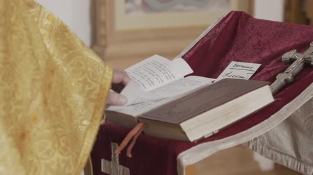 holy book : Orthodox priest prays standing to face the iconostasis.