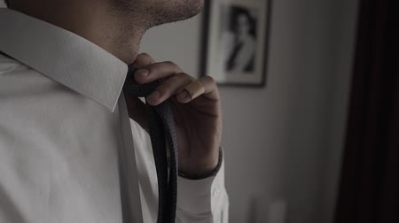аксессуары : Elegant business man in white shirt correcting his tie and buttoning his suit jacket. close up.