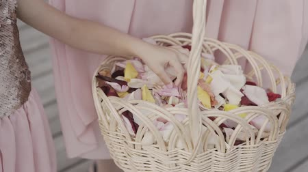 takes : Hand takes the rose petals from the basket.