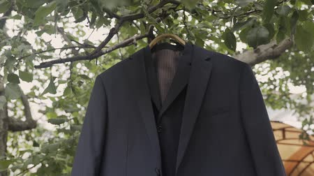 smokin : The brides jacket is hanging in a garden on a tree. Stok Video