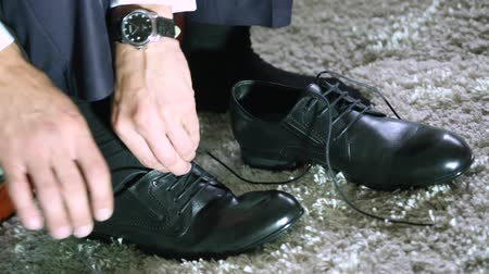 cipőfűző : Young man tying shoelace on sport shoes indoors, closeup. Stock mozgókép