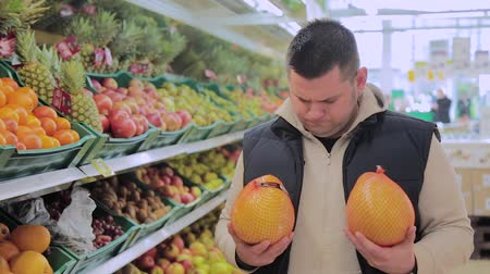 supermarket shelf : Fat man in the supermarket chooses fruit for himself.