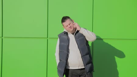 に対して : Fat man posing against a green wall near the store.