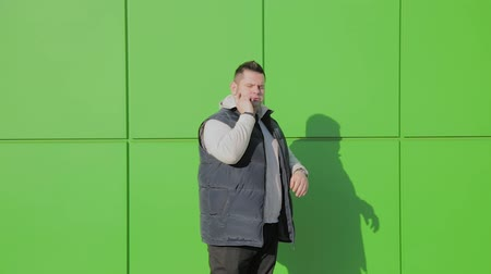 Çapraz kollar : Fat man posing against a green wall near the store.