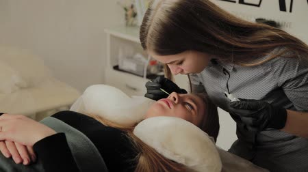 kozmetikus : A very beautiful girl in a beauty salon does a lamination lashes. Beautician performs the procedure eyelash fragmentation.