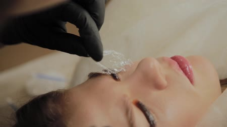 салон : A very beautiful girl in a beauty salon does a lamination lashes. Beautician performs the procedure eyelash fragmentation.