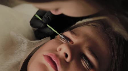 salon : A very beautiful girl in a beauty salon does a lamination lashes. Beautician performs the procedure eyelash fragmentation.