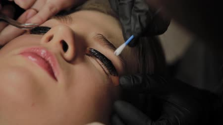 laminação : A very beautiful girl in a beauty salon does a lamination lashes. Beautician performs the procedure eyelash fragmentation.