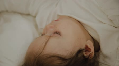 comfortable : Beautiful little girl sleeping in her cot. Stock Footage
