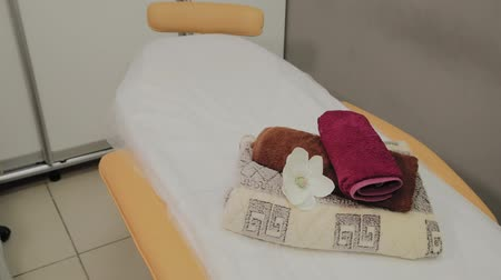 invite : Lounges for thai massage with towels, pillows and flowers in empty room. Stock Footage