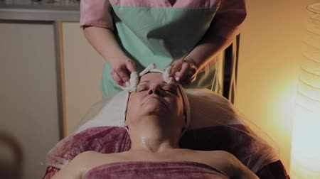 pomačkání : A professional beautician prepares the face of an elderly woman for the procedure. Cosmetological innovations