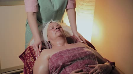 омоложение : Professional cosmetologist makes massage to an elderly woman. Cosmetological innovations
