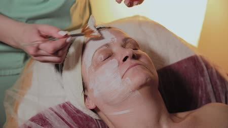 eye mask : A professional cosmetologist applies a face mask to an elderly woman. Cosmetological innovations. Stock Footage