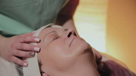 увлажняющий : A professional beautician prepares the face of an elderly woman for the procedure. Cosmetological innovations