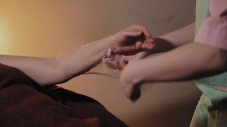 関節炎 : A professional cosmetologist removes cellophane from the hand of an elderly woman. Cosmetological innovations. 動画素材