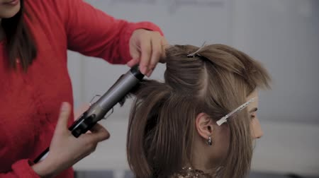 vlasy : Professional hairdresser does a girls hairstyle for a photo shoot.