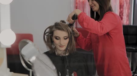 creative makeup : Professional hairdresser does a girls hairstyle for a photo shoot.