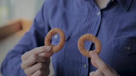 beer house : The girl holds onion rings in a fast food restaurant.