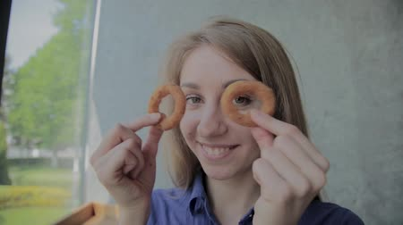 carne : The girl brings onion rings to her face and smiles in a fast-food restaurant.