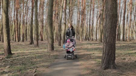wozek dzieciecy : Beautiful woman walking with her little daughter and pushing push stroller in park. Mom walks with a stroller in the park Wideo
