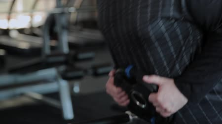 gymnasium : An overweight adult man performs hyperextension in a gym.