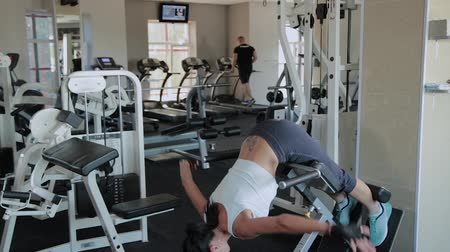 bil : Young beautiful woman performs hyperextension in the gym.