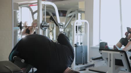 orange t shirt : An overweight adult man performs hyperextension in a gym.