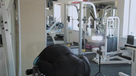 backbone : An overweight adult man performs hyperextension in a gym.