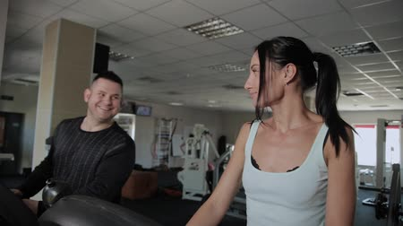 excesso : Beautiful athletic woman and a man with excess weight are training on a treadmill. Stock Footage
