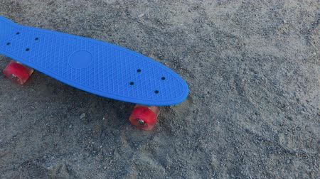 skateboard deck : Skateboard standing on the sand in bright weather.