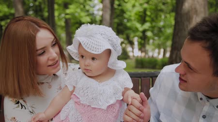 boeken : Happy young family with his son resting in the Park in the summer on a bench. A beautiful woman with her husband and a child sitting on a bench in the background of the urban landscape Stockvideo