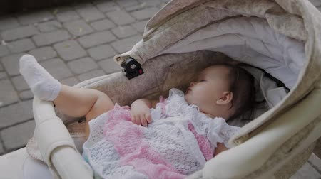 buggy car : Beautiful little girl sleeping in a baby carriage on the street.