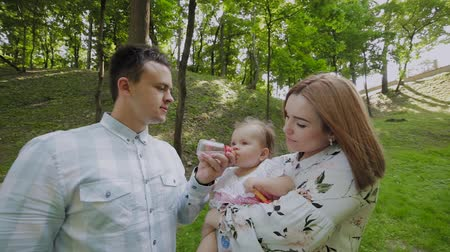 sağlamak : Young mom and dad bottle feed babies in the park on their hands.