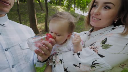 fed : Young mom and dad bottle feed babies in the park on their hands.