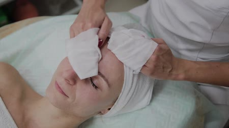 szalvéta : A woman is cleaned with special wipes in the beauty salon. Stock mozgókép