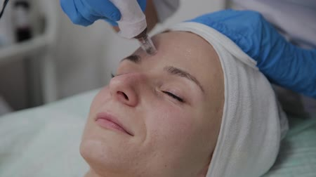 escovação : Professional cosmetologist performs DermaPen procedure in a cosmetology clinic.