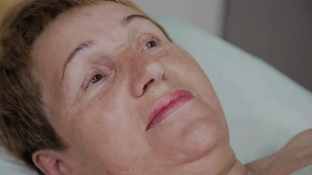 лифтинг : An elderly woman is lying on a couch in a cosmetology clinic.